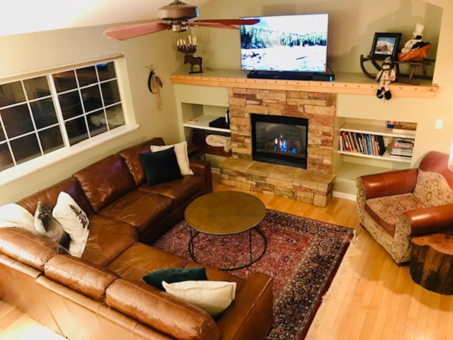 """Large living room right off kitchen / dining room with big windows, vaulted ceilings and great views.  55"""" TV over the fireplace has cable, DVD player, and internet connected apps (Netflix, Amazon, YouTube, etc.)."""