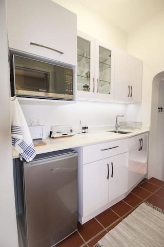 The kitchen does not have a stove but is equipped with a two plate hob with pots and pans, an electric frying pan and a microwave.