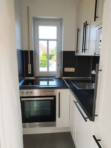 Küche mit Backofen, Ceranfeld, Spülmaschine, Mikrowelle, Kühlschrank, Toaster und vollständiger Küchenausstattung
