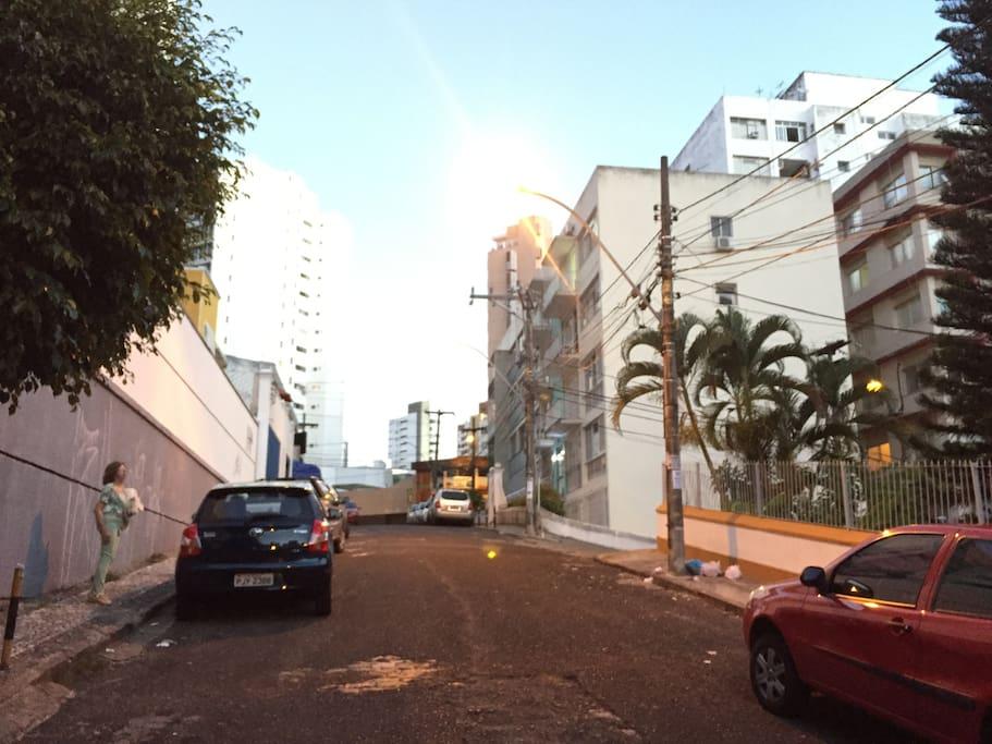 Rua local que dá acesso a bancos, farmácias, Correios, restaurantes, delicatessens e mercados.