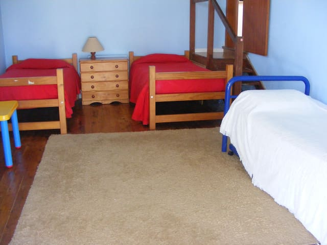 Bedroom with three single beds and one trundle bed.