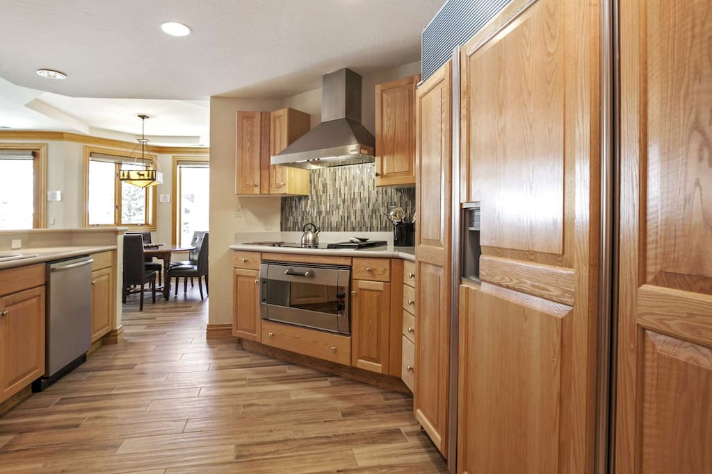Spacious fully equipped kitchen features Gaggenau oven, glass cooktop and stainless appliances.