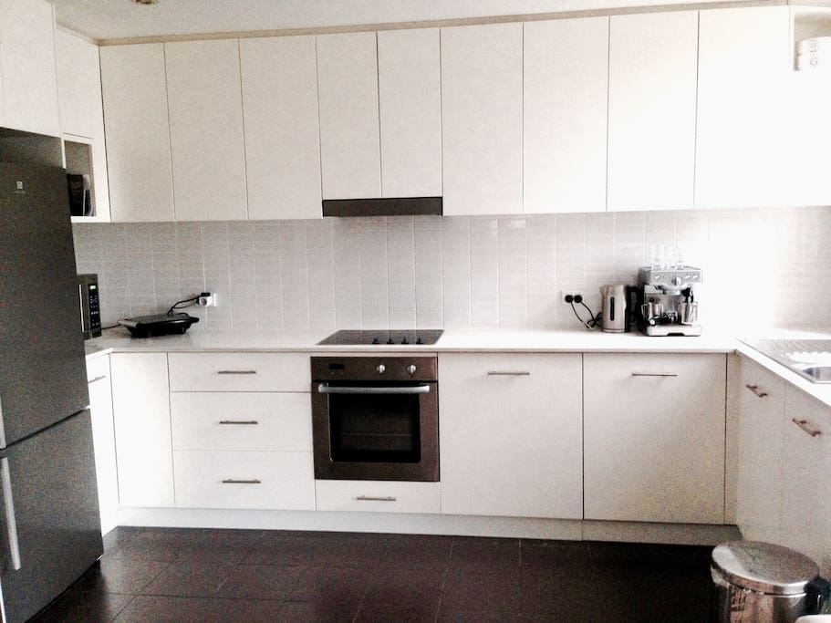 Large clean white kitchen with washing machine, dryer and big fridge.