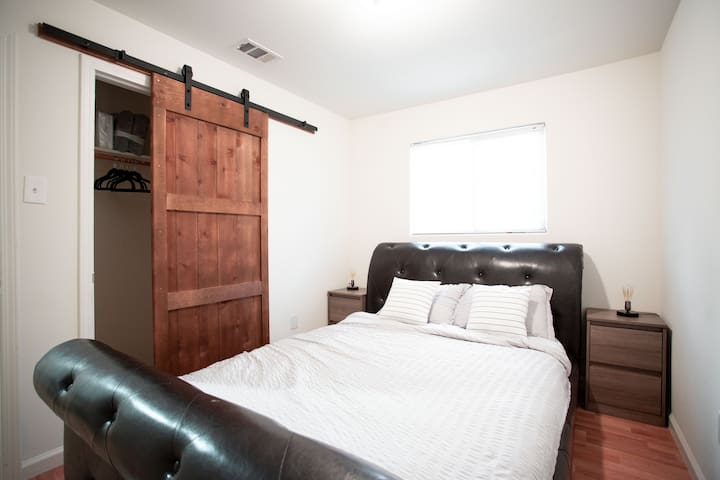 Bedroom #2. Comes with super comfy queen mattress on a sturdy solid wood bed frame, two night stand, desklamps, rug, multiple outlets, full closest with sliding barn yard doors to put your luggage, hang clothes and store all your personal belonging