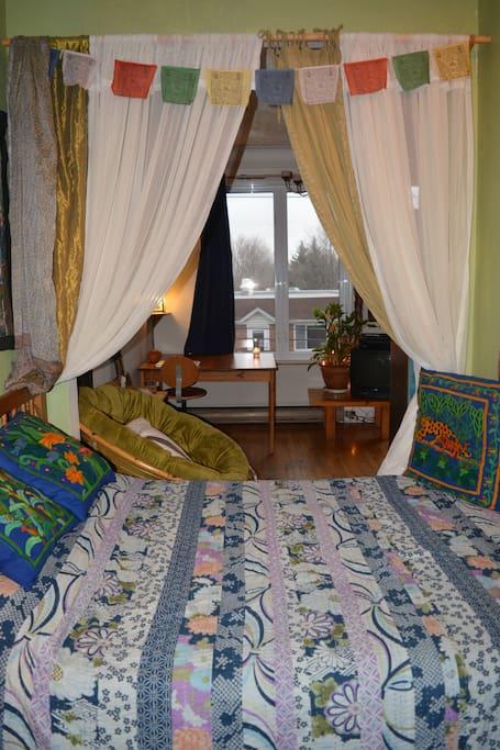 Chambre délimité par des rideaux.