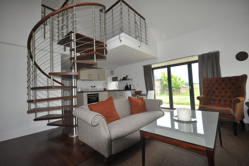 Open lounge with kitchenette and spiral staircase to sitting area and books.