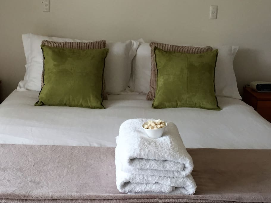 The queen bed in the main bedroom is made up with crisp quality linen