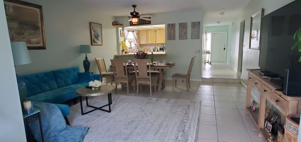 Living room with couch , coffee table in front of big TV/ roku sticks in all 4 rooms tv with roku sticks . Dining room with beautiful table 4 chairs and banch / breakfast bar countertop next to it with 4 swirl chairs
