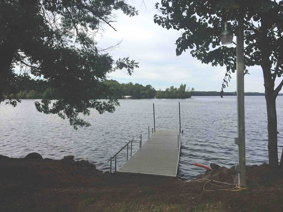 Wide dock with stairs down to sandy/rocky bottom. There is a light post with electrical outlet. Plenty of room for two boats to tie up with bumpers.
