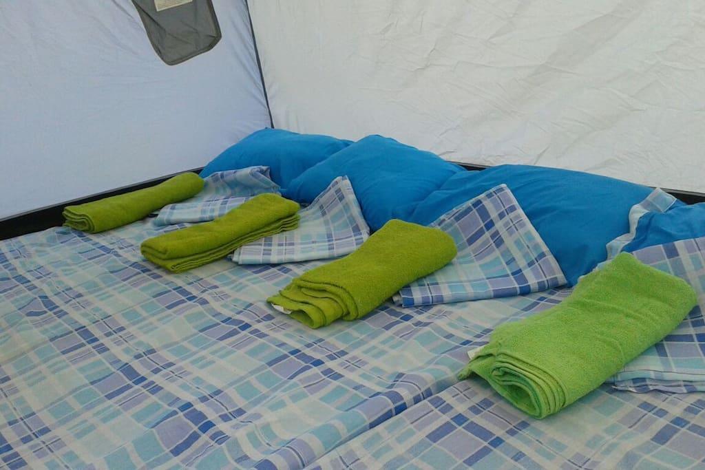 Tienda de campaña acondicionada con colchonetas y ropa de cama