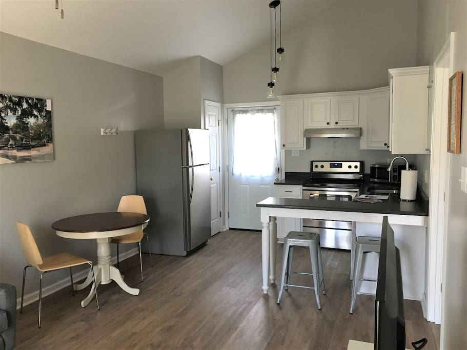 Open kitchen with dining table. Full sized oven, fridge, and dishwasher.