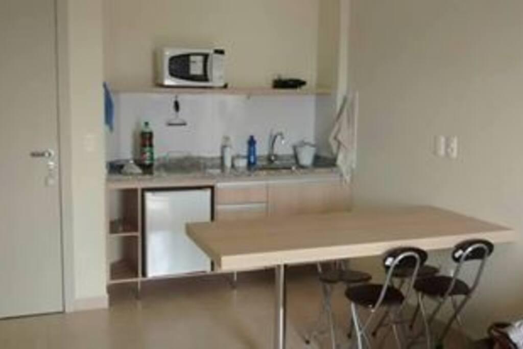 Cozinha equipada com microondas, frigobar, pratos, copos e talheres.