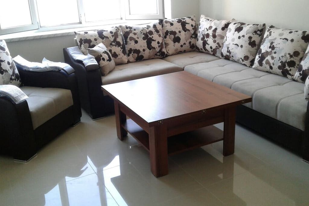 Newly furnished living room with comfortable sofas and extendable table beside a window overlooking the city and mt Ararat
