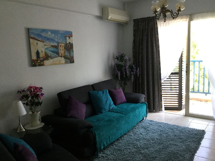Comfortable air-conditioned lounge area with patio door access to balcony