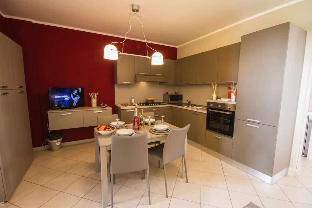Fully fitted modern kitchen with a dishwasher and a dining set