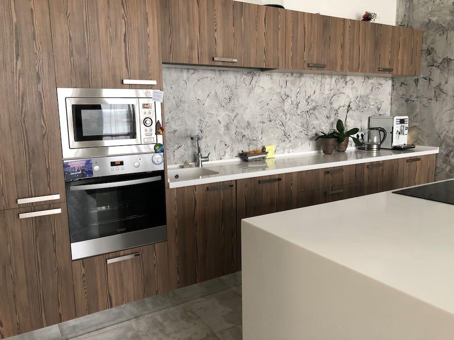 Кухня имеет микроволновку, духовой шкаф, кофе машину, электрическую плиту