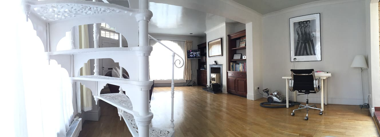 Gorgeous spiral staircase leading to the first floor - Spacious living room, with television, writing desk, sofa and wood burning stove.