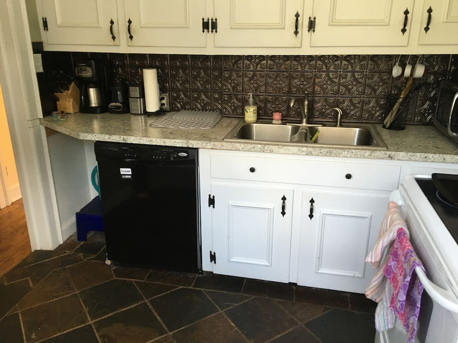 Kitchen has refrigerator, microwave, stove, oven and dishwasher, dishes, silverware, glasses, and mugs