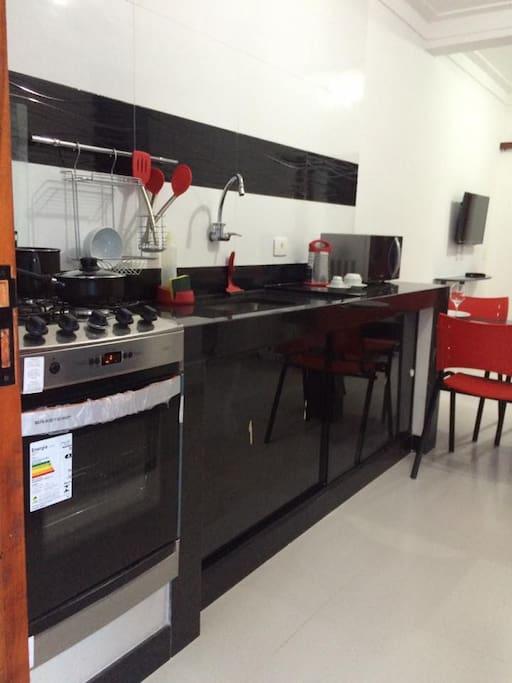 Cozinha equipada com utensílios básicos, refrigerador, fogão e microondas