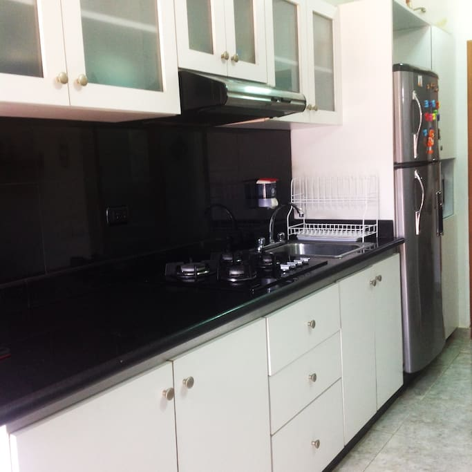 This is the cooking space. You can see the fan, cooktop, refrigerator and microwave at the end.
