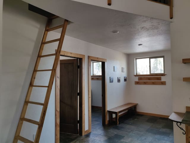 Entry has coat/hat hooks and boot/shoe box under bench.  Ladder to the loft.