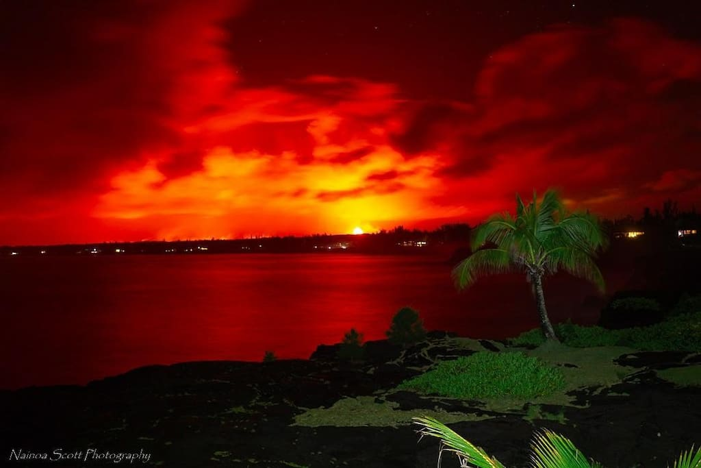 A view from the house at night looking at fissure 8 and the glow of the lava as it heads towards the ocean