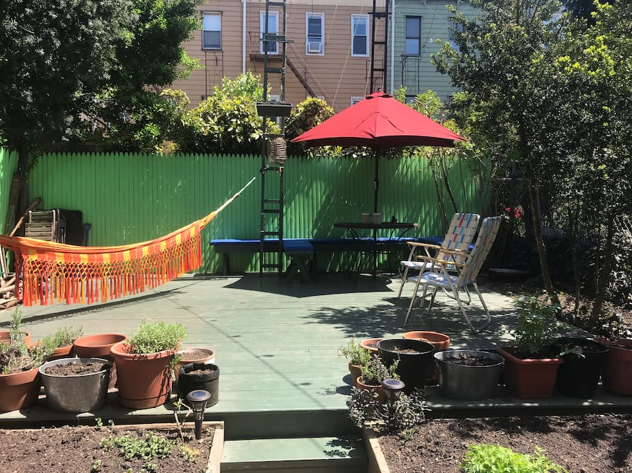 Private backyard with organic vegetable garden, hammocks, dining table & chairs & grill (updated w/ wood patio & benches)