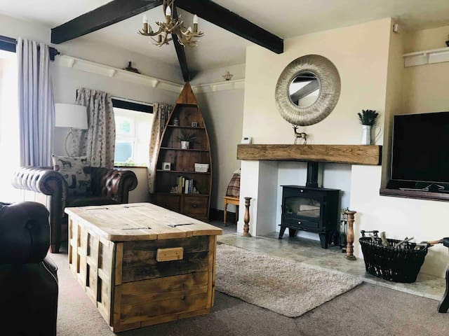 """Large living room with 49"""" flat screen Smart TV 4K ultra HD top of the range with Netflix and speedy unlimited internet. Perfect for flash nights in. Brand new log burning stove and some interesting books to read"""