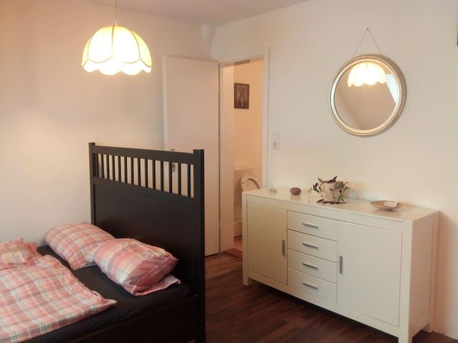 Das Bett, eine Kommode und die Tür zum Bad (WC,  Waschbecken)