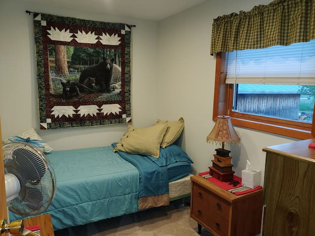 Third bedroom is a single bed, dresser, nightstand and small chest with extra bedding and table top fan.