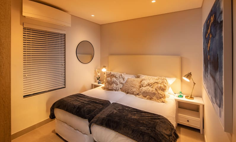 Bedroom two - two single beds that can be converted into a king size bed. Includes ample cupboard space and an air conditioner.