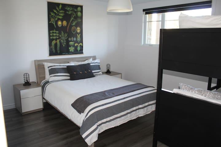 Chambre avec lit queen et lits superposés.