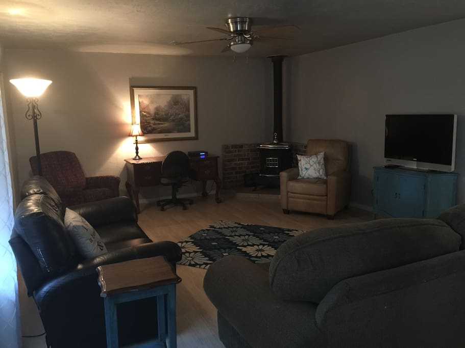 Large living room with desk area, television and dvd player.