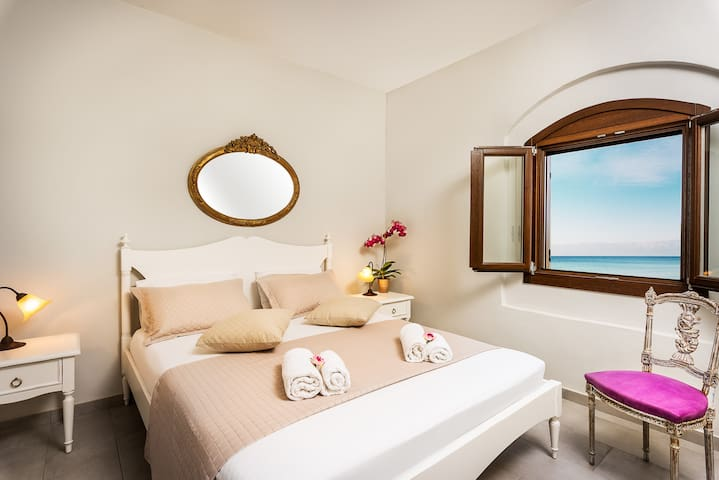 Romantic double bed in pal colours with a sea view.