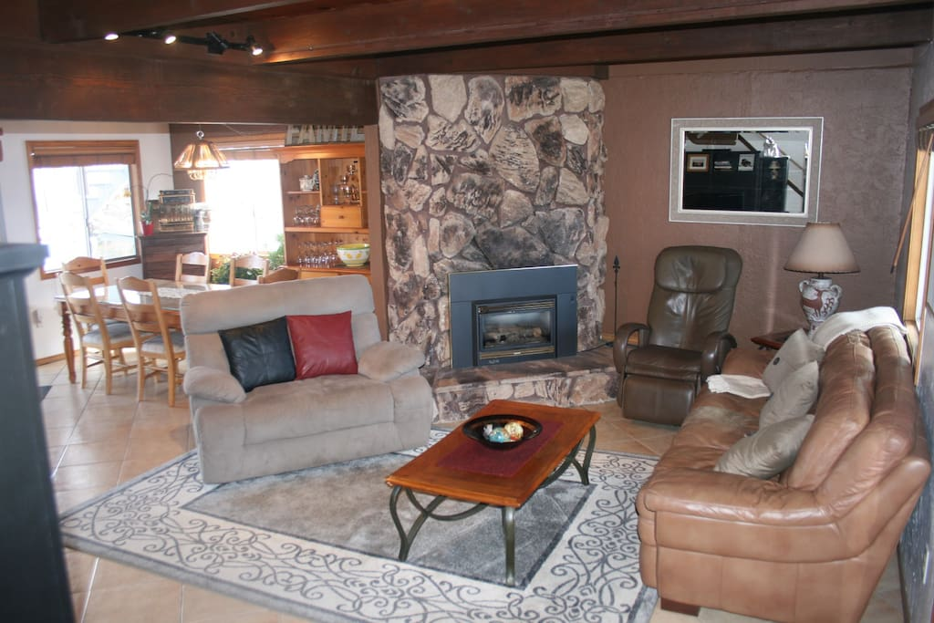 Open living room with plenty of seating, fireplace, & large flat screen tv.