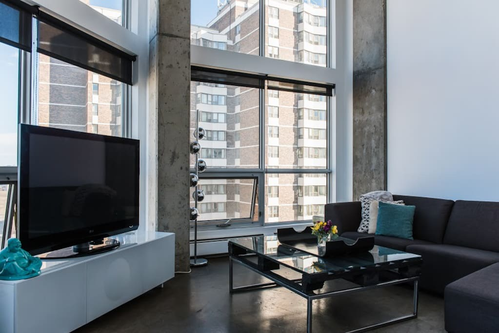 """Spacious and bright living room with a view of the river. Lounge on this huge EQ3 sectional couch and enjoy your favorite shows on this 50"""" tv with cable."""