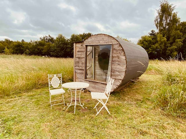 Rustic wooden glamping pod with lake view