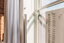 Original wood shutters provide light control and privacy.