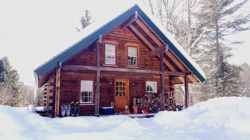 The front porch stocked with firewood for the wood stove and snow shoes for winter adventures. And one of our very social golden retrievers :)