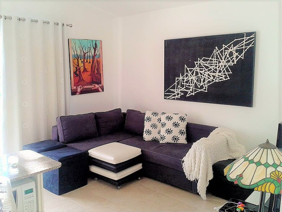 The livingroom of the apartment comes with a balcony, open kitchen, seating area, WIFI, AC and TV