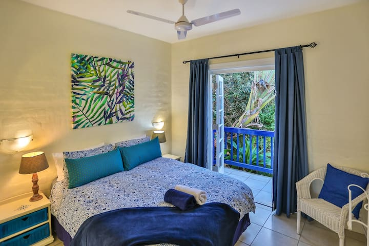 En suite main bedroom with double doors that open up on to a balcony overlooking a beautiful tropical paradise filled with the sounds of birds and sights of butterflies