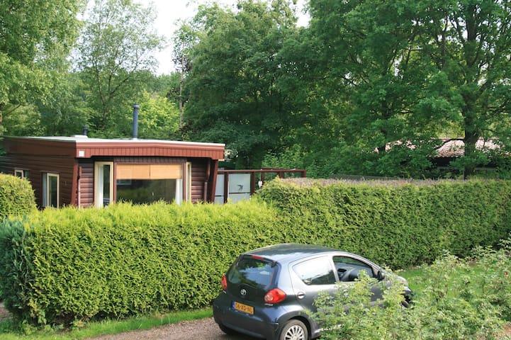 Houten stacaravan in bos en waterrijk Friesland
