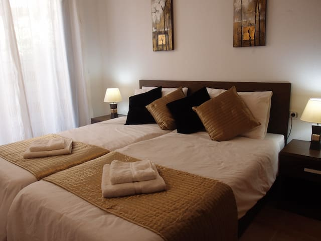 Main bedroom with two comfortable beds. Access to garden and en-suite bathroom.