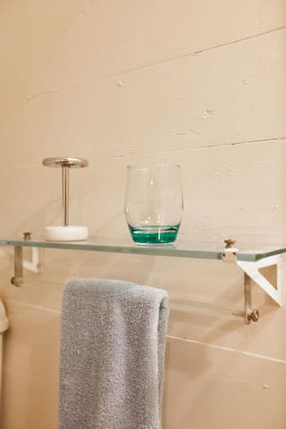 Detail of the glass shelf next to the bathroom mirror.