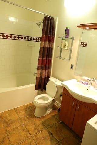 Bathroom with Washer & Dryer. Stocked with shampoo, conditioner, and lotion. Large tub and shower. Keep it clean!