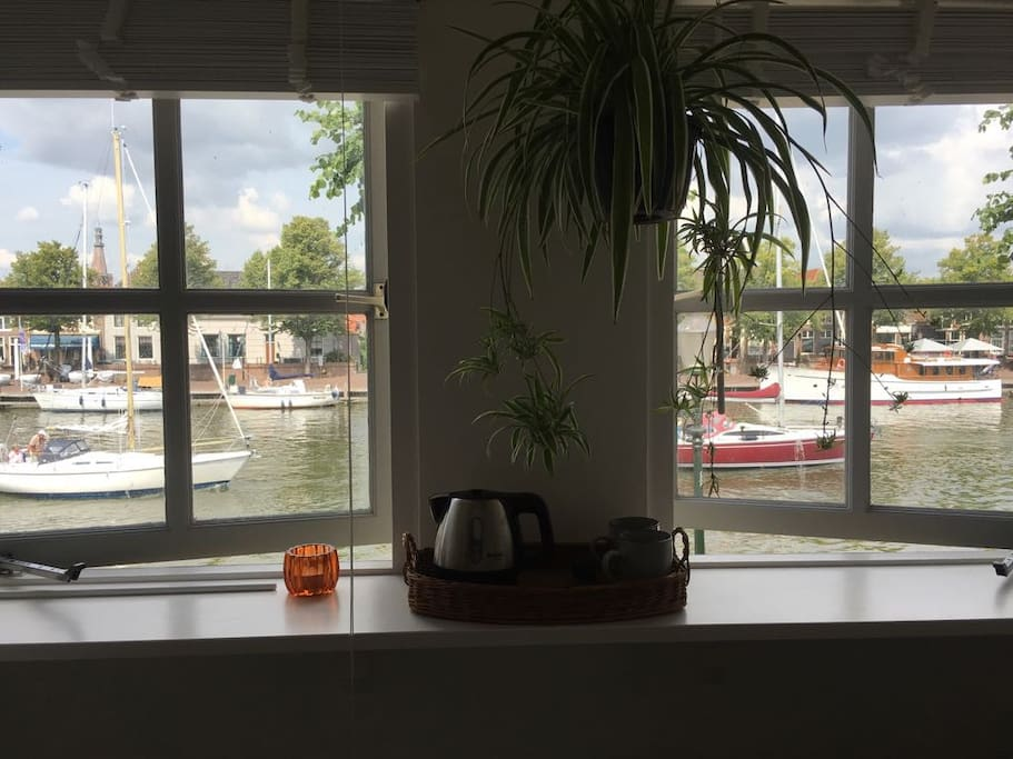 uitzicht slaapkamer op passerende schepen en boten aan de kade
