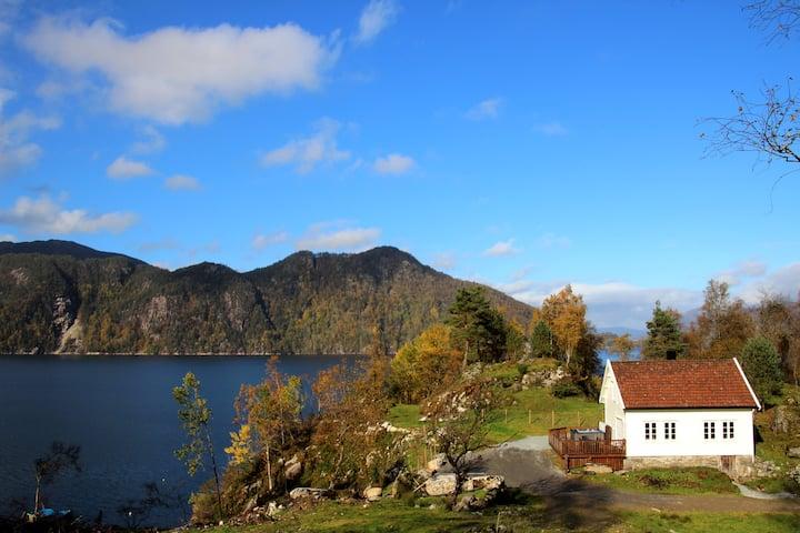 Koselig hus med boblebad og båt ved fjorden
