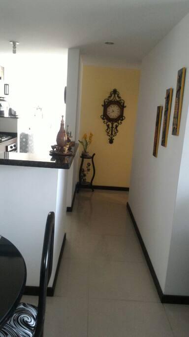 Corredor principal del apartamento, cocina abierta.