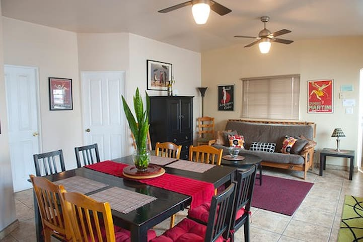 This is our large dining table, our futon is seen on the background (which converts into a bed that fits two) to the left, the TV is hidden inside our black cabinet.