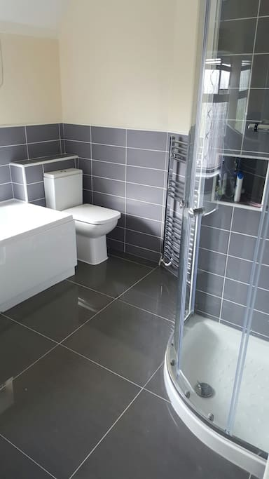 Brand new bathroom with shower cubicle and separate bath